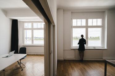 Businesswoman in office looking out of window - KNSF01815