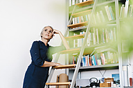 Businesswoman in office leaning against a ladder - KNSF01818