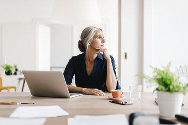 Businesswoman working on laptop in office - KNSF01821
