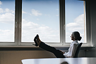Businesswoman in office sitting at the window looking out - KNSF01824