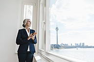 Businesswoman looking out of window in waterfront office - KNSF01830