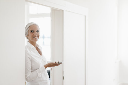 Portrait smiling businesswoman holding cell phone in office - KNSF01839