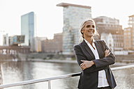 Confident businesswoman standing on bridge - KNSF01842
