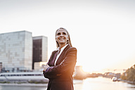 Confident businesswoman outdoors at sunset - KNSF01845
