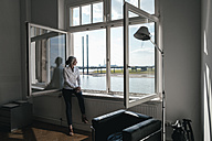 Businesswoman sitting on windowsill - KNSF01854