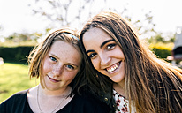 Portrait of two smiling girls outdoors - MGOF03425