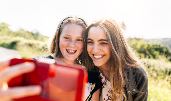 Two happy girls taking a selfie outdoors - MGOF03428
