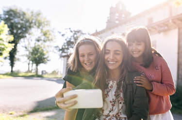 Three happy girls taking a selfie outdoors - MGOF03440