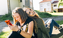 Two happy girls using their smartphones outdoors - MGOF03443