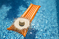 Straw hat on orange airbed in swimming pool - MAEF12349