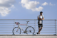 Young man with racing bicycle having a break - FKF02430