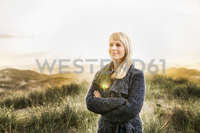 Smiling woman standing in dunes - FMKF04200