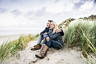 Couple sitting in dunes - FMKF04203