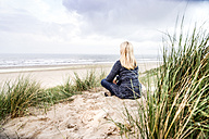 Woman sitting in dunes - FMKF04209