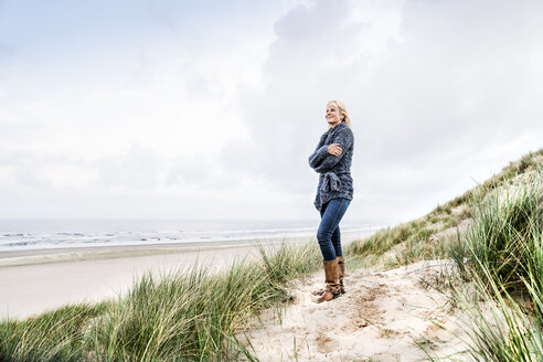 Smiling woman standing in dunes - FMKF04212