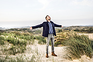 Man standing in dunes with outstretched arms - FMKF04221
