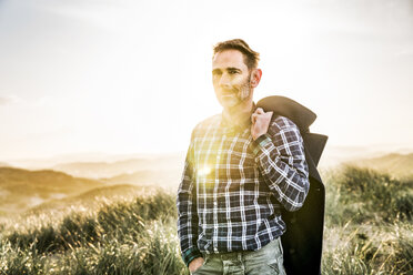 Portrait of man standing in dunes at sunset - FMKF04227
