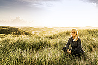 Smiling woman sitting in dunes - FMKF04230