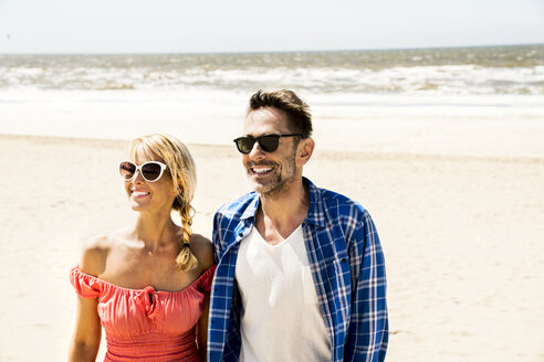 Happy couple wearing sunglasses on the beach - FMKF04236
