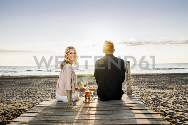 Couple with wine glasses sitting on boardwalk on the beach at sunset - FMKF04242