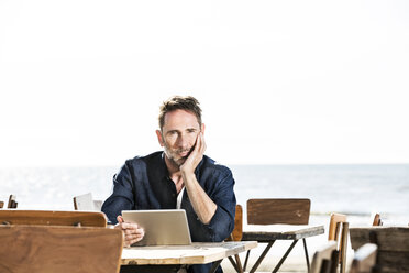 Man with tablet sitting in a cafe on the beach - FMKF04245