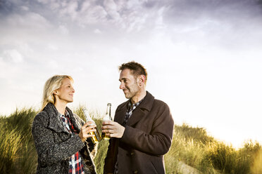 Smiling couple in dunes clinking beer bottles - FMKF04248