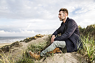 Man sitting in dunes - FMKF04257
