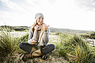 Smiling woman sitting in dunes using cell phones - FMKF04260