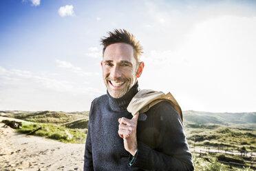 Portrait of happy man in dunes - FMKF04263