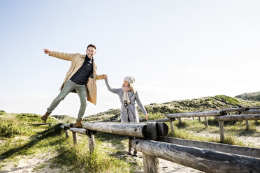 Woman helping man balancing on wooden stakes in dunes - FMKF04266