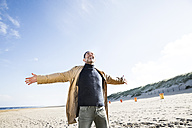 Happy man standing on the beach with outstretched arms - FMKF04269
