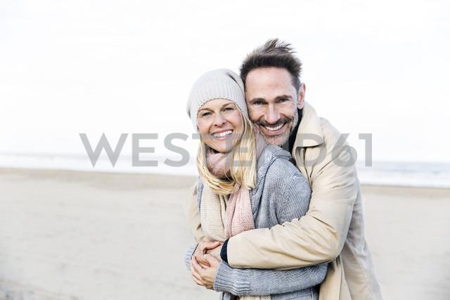 Portrait of happy couple hugging on beach - FMKF04272