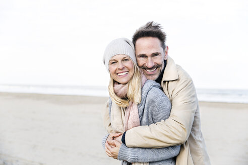 Portrait of happy couple hugging on beach - FMKF04272