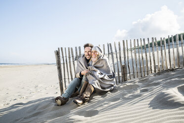 Smiling couple wrapped in blanket on the beach - FMKF04275