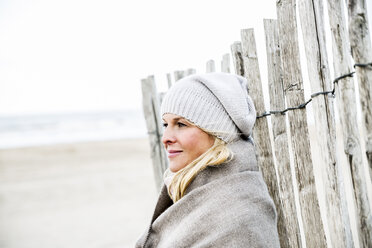 Smiling woman at fence on the beach - FMKF04278