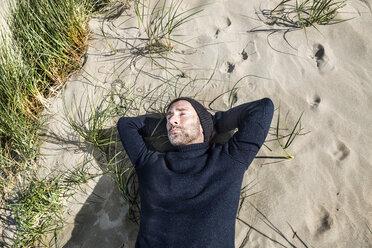 Man wearing woolly hat lying in beach dune - FMKF04284
