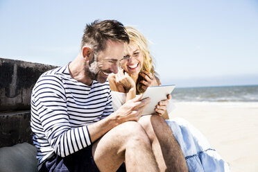 Happy couple on the beach looking at tablet - FMKF04290