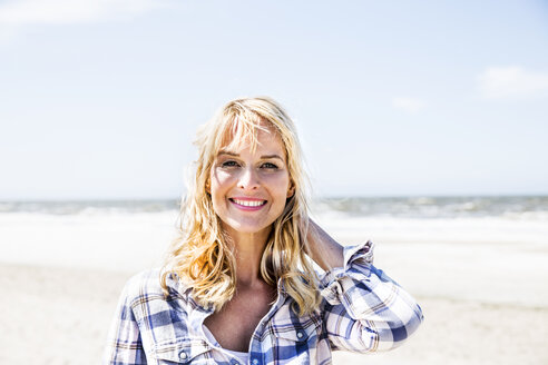 Portrait of smiling woman on the beach - FMKF04296