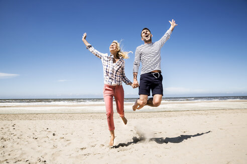 Happy carefree couple on the beach - FMKF04299