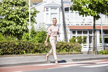 Smiling woman crossing a street - FMKF04305