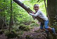 Portrait of little girl climbing on tree in the woods - DIKF00261