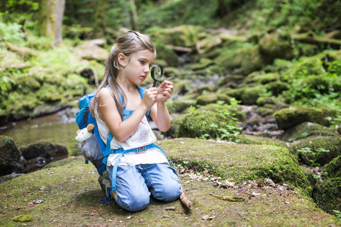 Little girl with magnifier crouching on rock in the woods watching a feather - DIKF00267