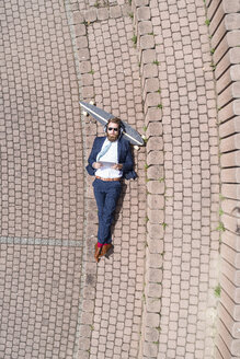 Businessman with skateboard lying on a wall using tablet and headphones - MAEF12358