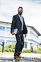 Portrait of businessman with sunglasses and tablet standing on skateboard - MAEF12364