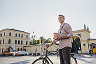 Smiling man with bicycle and takeaway coffee in the city - DIGF02559