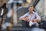 Man sitting on stairs with takeaway coffee in the city checking the time - DIGF02565