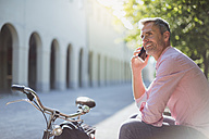 Smiling man with bicycle on the phone on a park bench - DIGF02571