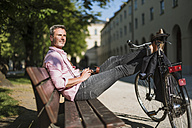 Man with bicycle and old-fashioned camera relaxing on a park bench - DIGF02574