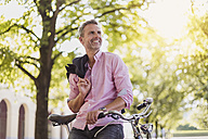 Smiling man with bicycle in a park - DIGF02577