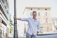 Portrait of happy man at lamp pole in the city - DIGF02583
